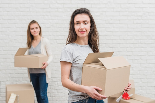 Lesbian woman holding the moving cardboard box and her girlfriend standing at background