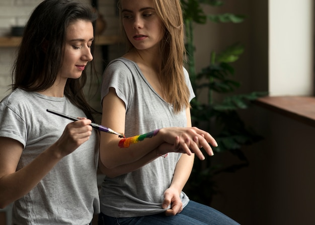 Lesbian woman painting the rainbow flag on her girlfriend's hand with paintbrush