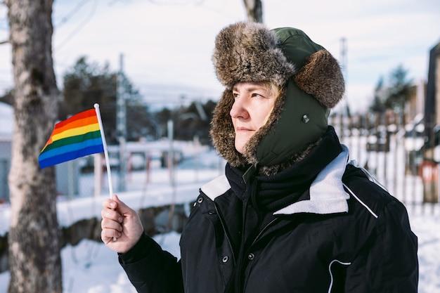 Лесбиянка в снежной шапке для волос в заснеженной местности держит радужный флаг лгбт