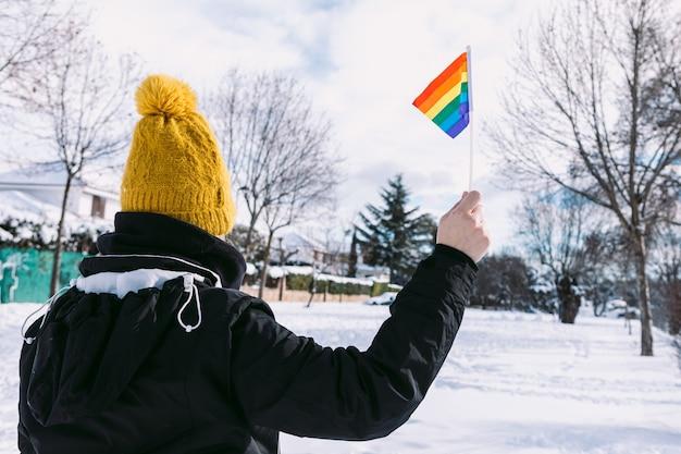 Лесбиянка в желтой снежной шапке повернулась спиной в заснеженной местности с радужным флагом лгбт