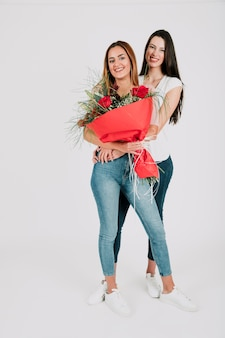 Lesbian women with bunch of flowers embracing