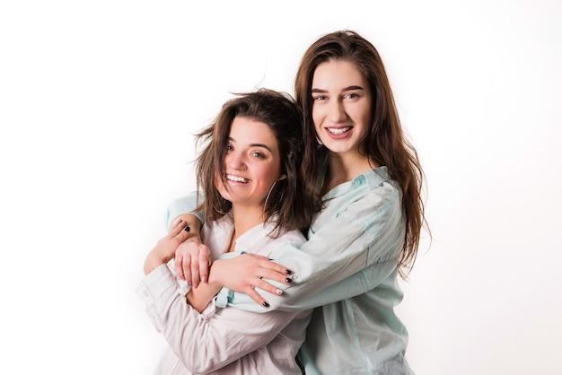 Молодая лесбийская пара обнимается на белом фоне