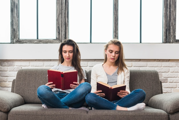 Lesbian young couple sitting on grey sofa with crossed legs reading book