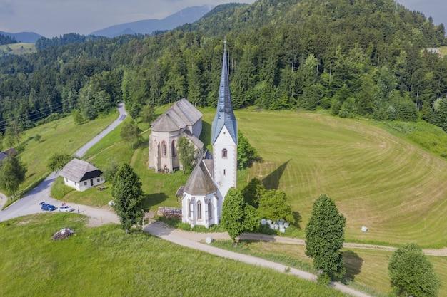 スロベニアの日光の下で緑に覆われた丘の上のlese教会