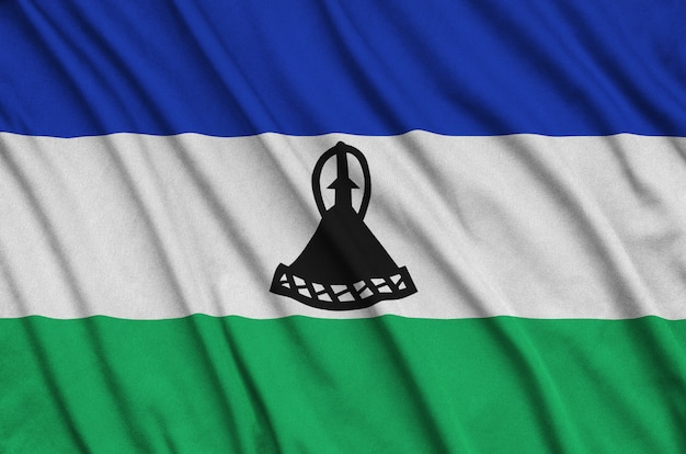 Lesotho flag  is depicted on a sports cloth fabric with many folds.