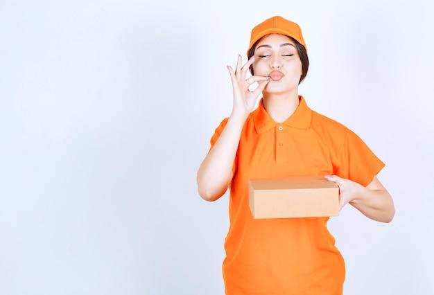 より少ない言葉でより多くの仕事を。静かに身振りで示すパッケージを持つ若い配達女性