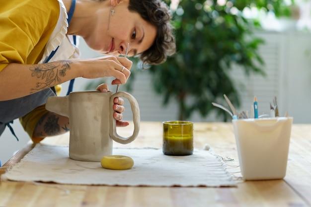 워크숍 예술가 여성의 도자기 수업은 도예가를 만들기 위해 도자기와 점토로 일하는 법을 배웁니다.