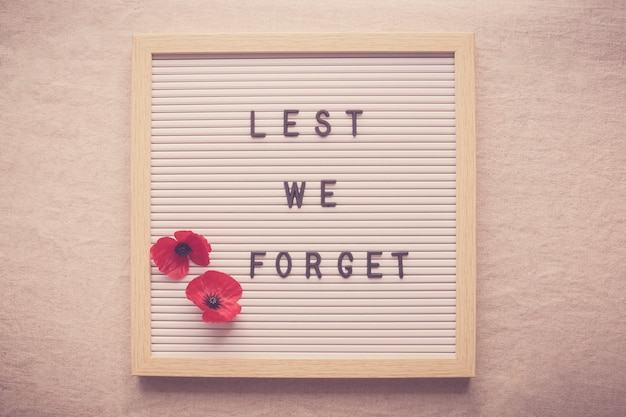 Lest we forget and red poppy flowers on letter board