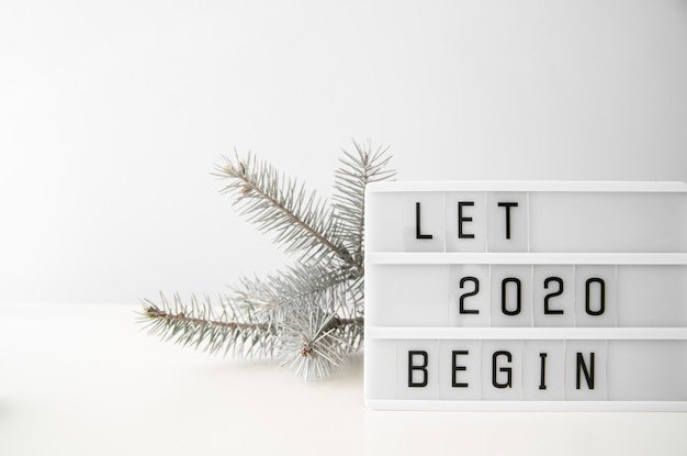 Let 2020 new year begin digits and silver christmas tree leaves