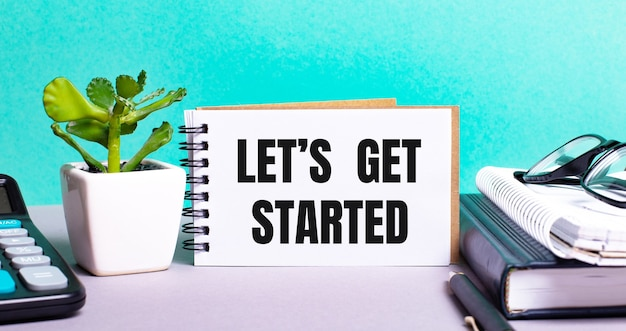 Let is get started is written on a white card next to a potted flower, diaries and calculator