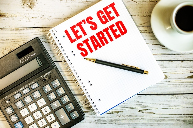 Let is get started written on white paper near coffee and calculator on a light wooden table. business concept
