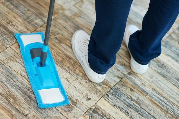 바닥을 청소하는 동안 걸레를 사용하여 남자 전문 남성 청소기의 클로즈업 샷을 청소하게 하십시오