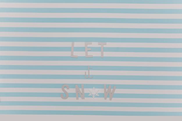 雪を降らせましょう。白と青の縞模様の壁に美しい新年の冬の碑文。