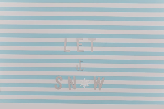 Let it snow. beautiful new year winter inscription on white and blue striped wall.