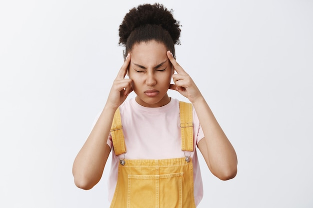 Let me concentrate shh. portrait of intense focused good-looking african american in yellow overalls, closing eyes, holding fingers on temples, trying reduce headache or remember information