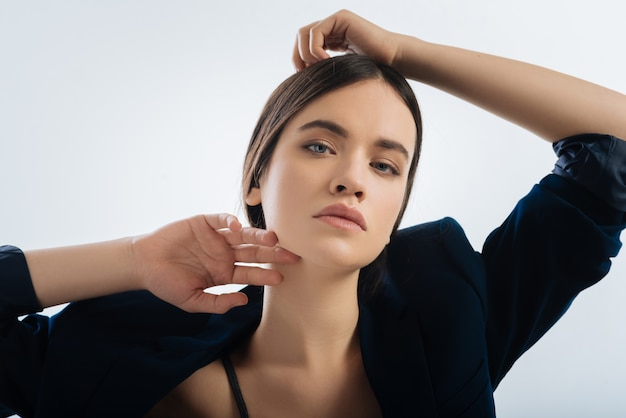 Let me go. earnest pleasant focused  woman touching her head  while  seducing with look and  gazing straight