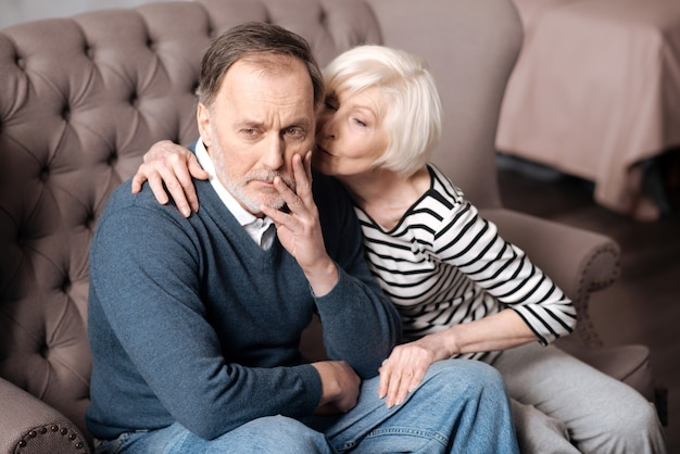 Позвольте мне помочь. довольно пожилая женщина целует своего бедного мужа с ужасной зубной болью.