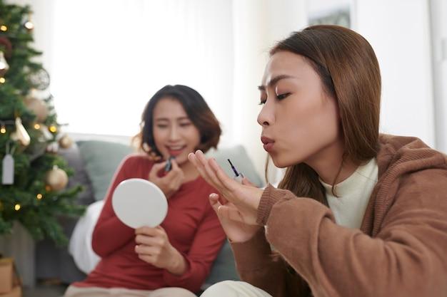 手伝わせてください。彼女の親友と一緒に座って、彼女の顔にいくつかの化粧をしているきれいな女性