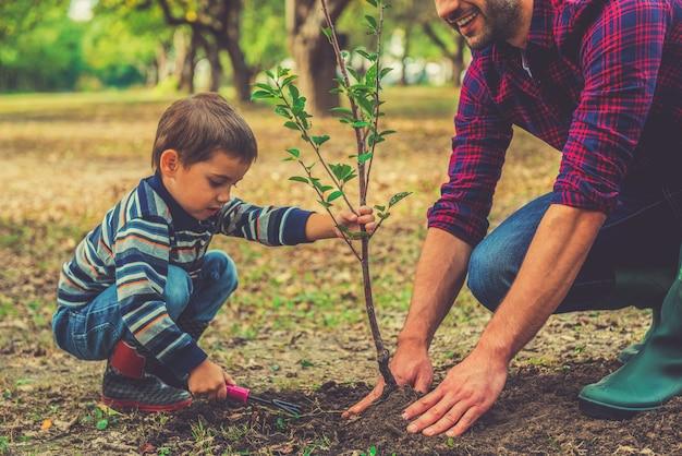 내가 도와 줄게! 정원에서 함께 일하는 동안 아버지가 나무를 심는 것을 돕는 어린 소년
