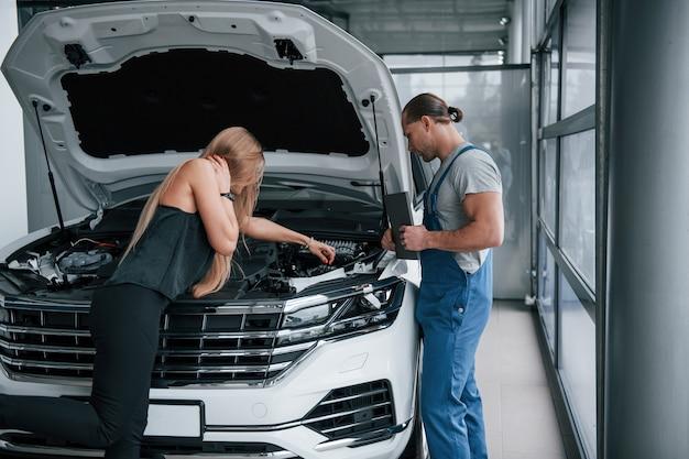 Позвольте мне помочь вам. результаты ремонта. уверенный мужчина показывает, какие повреждения получила ее машина.