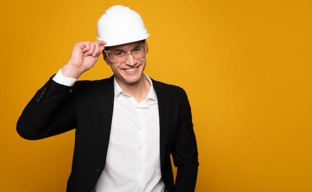 제 소개를하겠습니다. 소송에서 젊은 잘 생긴 남자는 카메라를보고 웃 고있는 동안 그의 하드 모자를 팁입니다.