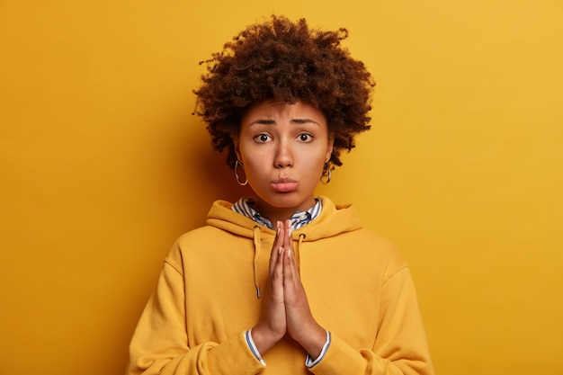 Let me please. sad pleading african american woman asks for permission, holds hands in pray, says forgive me, poses against yellow wall, wears sweatshirt. begging and saying forgive me.