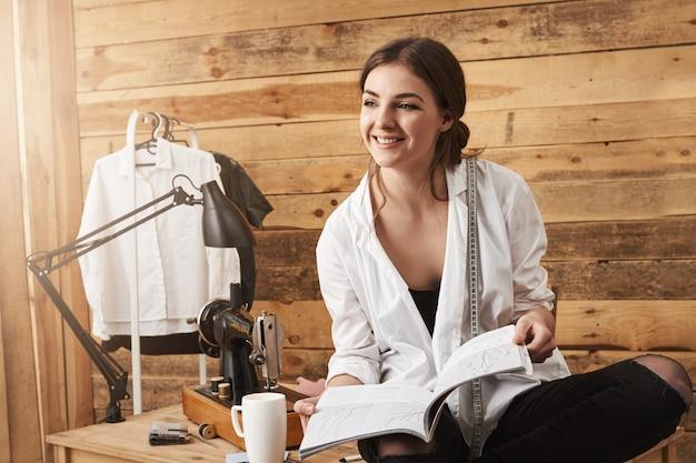私の新しいプロジェクトをお見せしましょう。幸せな創造的な女性のテーラーがテーブルの上に座って、縫製スキームを保持し、同僚と話し、ワークショップ用に新しい衣服を縫う方法を計画