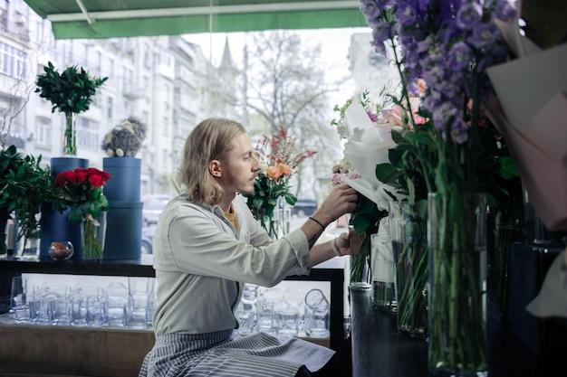 생각 해보자. 세심한 금발 플로리스트 꽃병에서 꽃다발을 가져 와서 세미 위치에 앉아