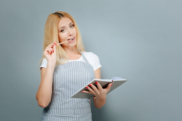 Let me think. attractive woman standing isolated on grey background and holding notebook while looking at camera