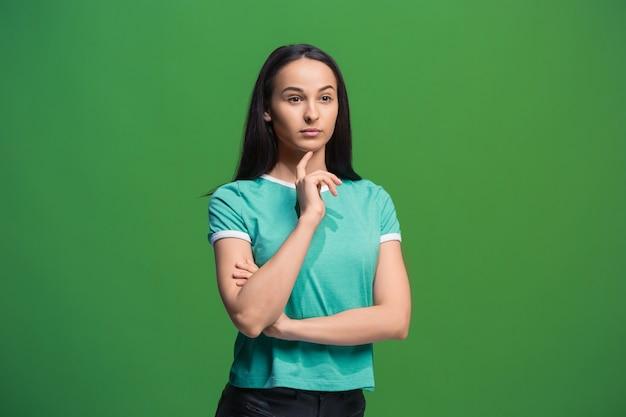 Дай мне подумать. концепция сомнения. сомнительная задумчивая женщина с задумчивым выражением лица, делающая выбор. молодая эмоциональная женщина. человеческие эмоции, концепция выражения лица. фронт . студия. изолированные на модном зеленом