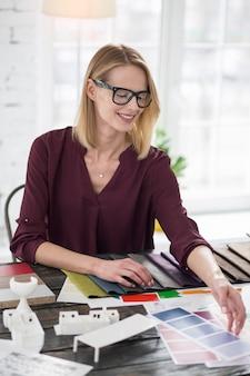 考えさせて。色を拾いながらサンプルの手を伸ばすエネルギッシュな女性デザイナー
