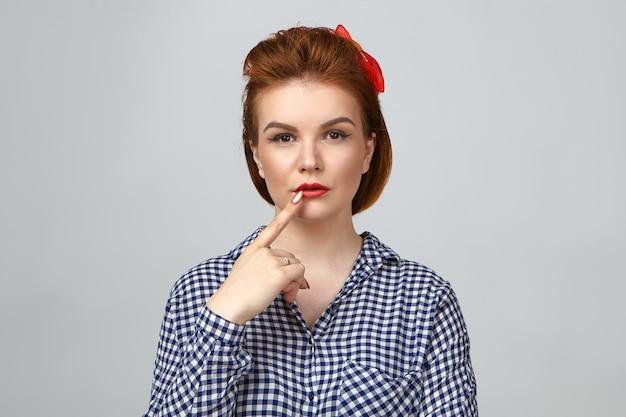 Fammi pensare. immagine isolata della giovane donna europea elegante alla moda con i capelli rossi che hanno in profondità nei pensieri espressione facciale pensierosa, toccando le labbra, cercando di ricordare qualcosa di importante