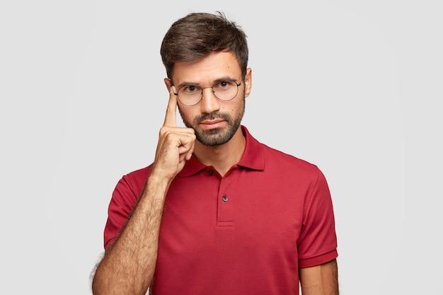 생각 해보자. 수염과 콧수염을 가진 심각한 형태가 이루어지지 않은 남자는 성전에 검지 손가락을 유지합니다.