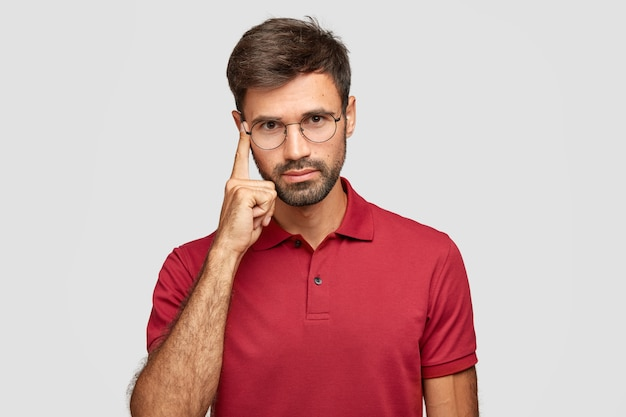 Let me think. serious unshaven man with beard and mustache, keeps index finger on temple