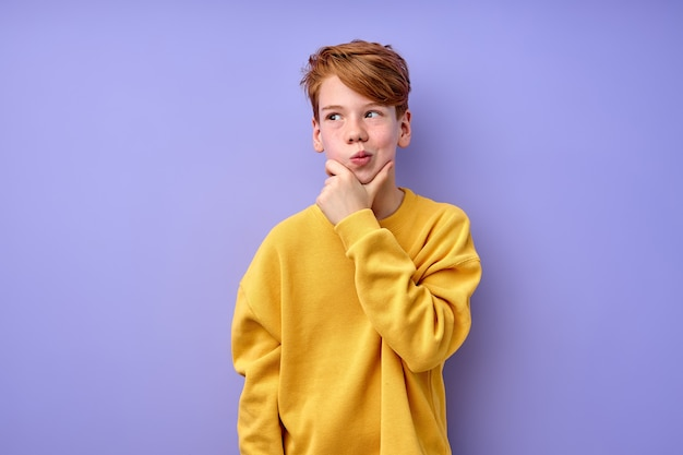 考えさせて。困惑した真面目な表情で黄色いシャツを着た思慮深い賢い赤毛の学者、子供は疑って考え、選択をします。紫色の背景に分離された屋内スタジオショット