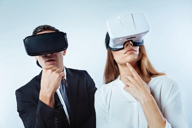 생각 해보자. 사려 깊은 동료들이 서로 옆에 서서 배경 위에 3d 시각 현실 헤드셋을 착용하고 꿈을 꾸고 있습니다.