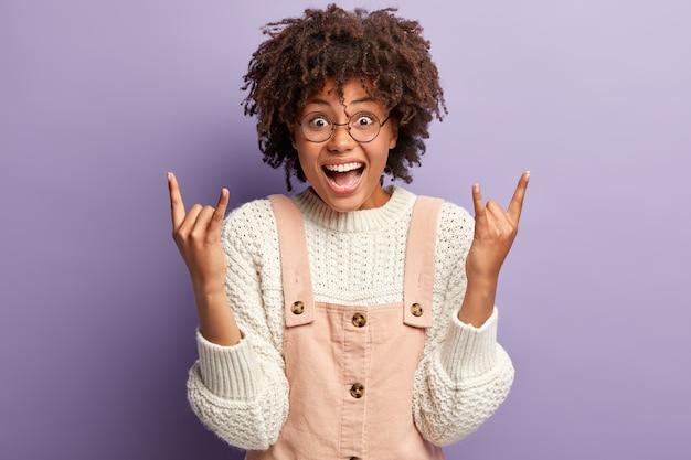 転がしてみましょう。ゴージャスな面白い女性はロックンロールジェスチャーで手を上げ、積極的にニヤリと笑い、楽しんで、幸せを表現します