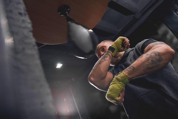 한번 붙어 준비하자. 팔 운동, 녹색 손을 가진 전문 젊은 권투 선수는 복싱 체육관에서 펀칭 스피드 백을 친다