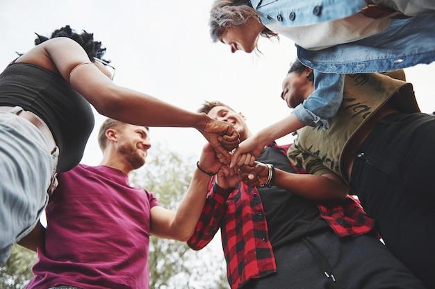 Давайте начнем эту вечеринку. многонациональная группа людей устраивает вечеринку на открытом воздухе. вид снизу.