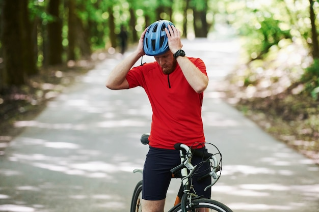 Let's go. cyclist on a bike is on the asphalt road in the forest at sunny day