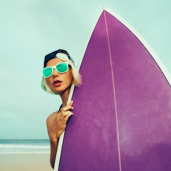 サーフィンに行きましょう。ビーチでサーフボードを持つ女の子
