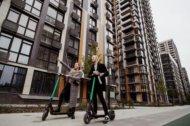 行きましょう!借りた電動スクーターで運転したい場所を手で見せている女性。彼女の話を聞いて笑っている男。幸せなカップル。パブリックシェア用の電動スクーター。