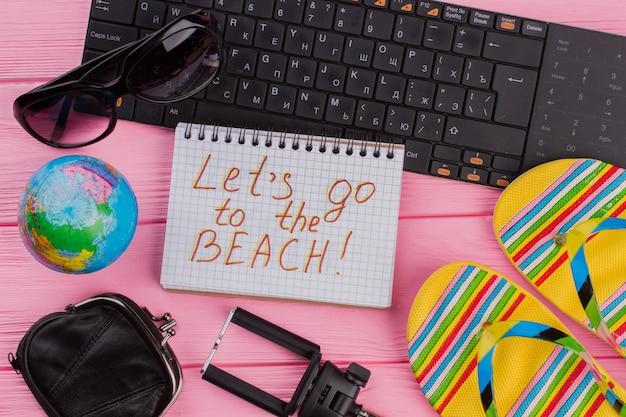 ピンクのテーブルトップの背景に女性の旅行者アクセサリーメガネ財布とビーチサンダルを持ってノートブックでビーチに行きましょう。グローブと黒のキーボード。