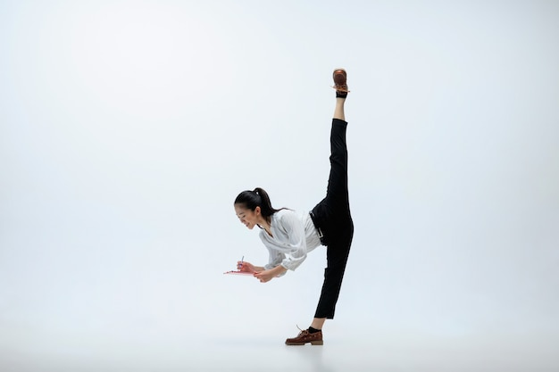 Immaginiamo il futuro e scriviamolo. donna felice che lavora in ufficio, saltando e ballando in abiti casual o vestito isolato su sfondo bianco studio. business, start-up, concetto di lavoro open-space.