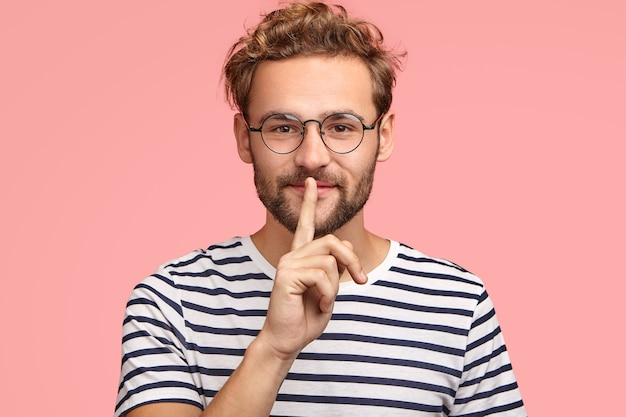 Let`s keep it in secret! handsome hipster makes shh gesture as spreads rumors, shows hush sign with index finger, dressed casually, isolated over pink wall. people, secrecy, conspiracy concept