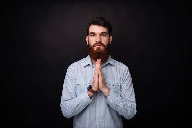 기도합시다! 수염을 기른 젊은 남자가 검은 배경에 기도하는 자세로 손을 잡고 있습니다.