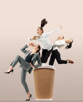 Начнем с ароматного кофе. счастливые офисные работники прыгают и танцуют в повседневной одежде или костюме с горячими вкусными напитками, изолированными на стене студии