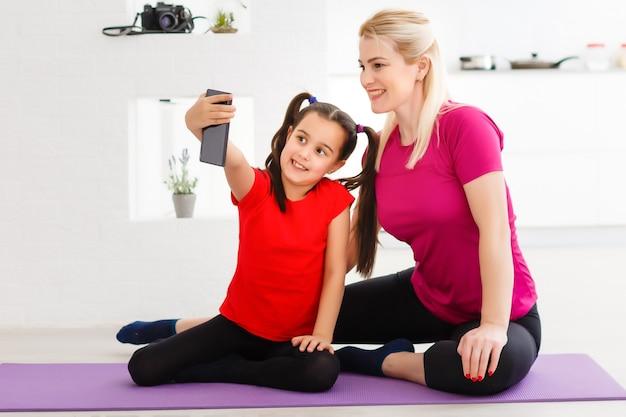 소셜 네트워크용으로 사진을 찍어봅시다. 스포티한 옷을 입고 인터넷 연결을 통해 화상 통화를 하는 아름다운 스포티하고 귀엽고 부드러운 엄마와 딸의 초상화를 닫습니다
