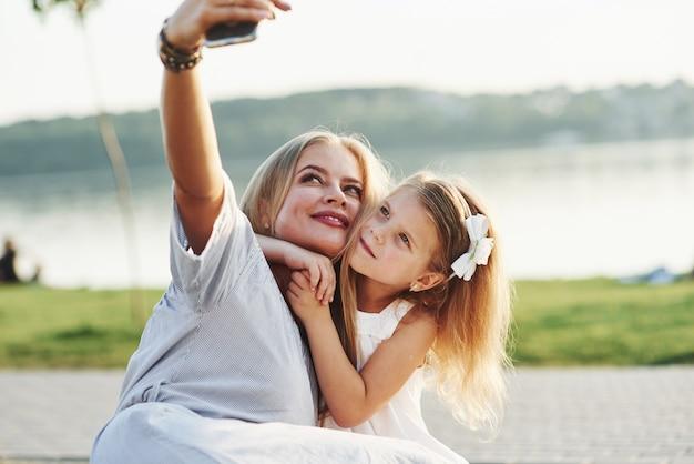 自撮りしましょう。湖を背景に緑の芝生で楽しい時間を過ごしている若い母と娘の写真。