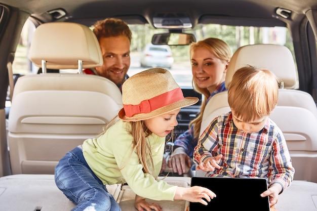 車の家族の道の中で遊んでいるwifiが弱いかわいい子供たちがいるところをさまよいましょう
